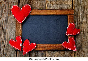 Toy hearts on a frame with a chalkboard