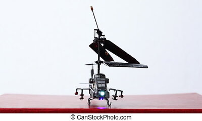 toy helicopter is on table, its blades start to rotate, then...