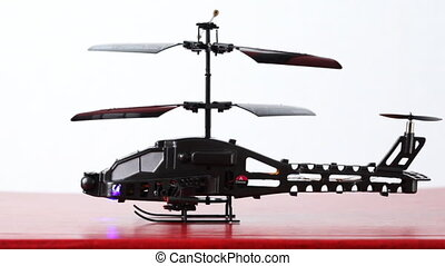 toy helicopter is on table, its blades rotate, then flies up...
