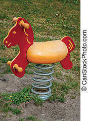 Toy horse for children in playground on a cloudy day at Drimmelen.
