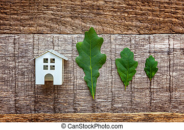 Toy House and green oak leaves on wooden background