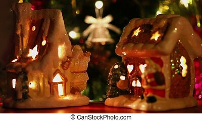 toy house-candlestick stand at background of christmas tree ornaments