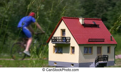 toy house in park, unfocused group from bicyclists riding past