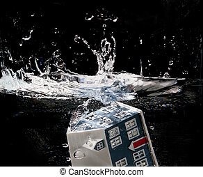 Toy house sinking underwater on a black background