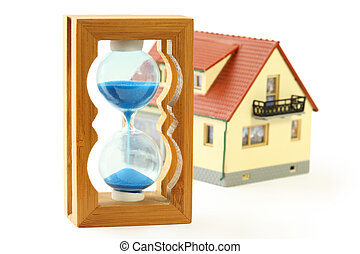 toy house with red roof and hourglass with blue sand isolated on white
