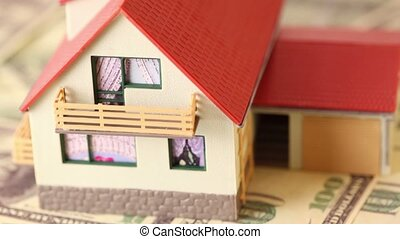Toy house with red tiled roof on dollars bank notes
