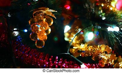 toy in form of glass grapes hanging on Christmas tree among glowing garlands