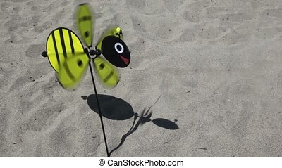 Toy in the shape of a bee with a rotating propeller stuck in the ground