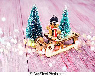 Toy in the shape of a Christmas tree, gingerbread cookie. toy snowman on a sled