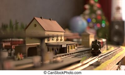 Toy locomotive moving through model train station. Model of ...