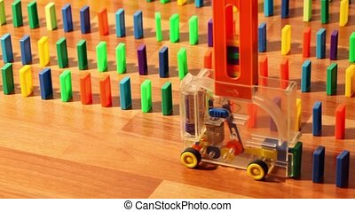 Toy machine moves and put colored domino blocks, view from...