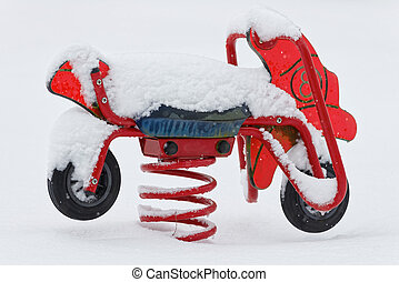 Toy motorcycle in a park during the winter