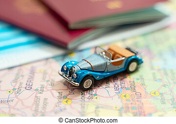 Toy of a car, medical mask and passport on the Europe map.