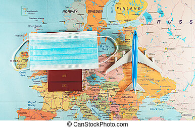 Toy of a plane, medical mask and passport on the Europe map.