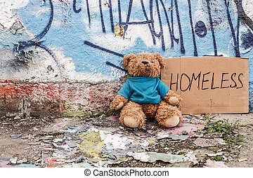 Teddy bear left on the ground near sign of homeless kid
