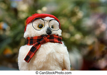Toy owl with glasses and scarf on the background of the Christmas tree