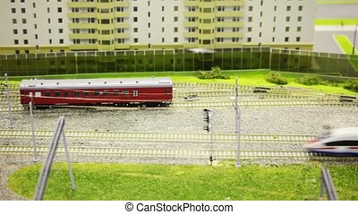 toy passenger express train stops on rail in toy modern sity...