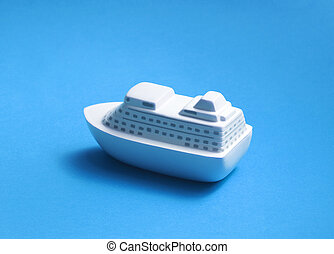 Toy passenger ship on blue background