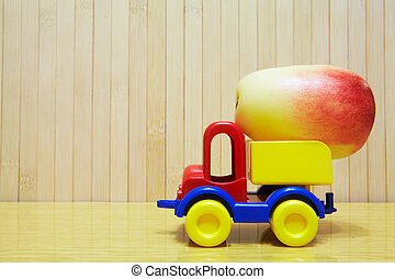 Toy plastic car with red apple