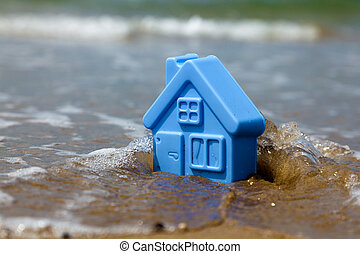 Toy plastic house on the sand washes wave - Blue toy plastic...