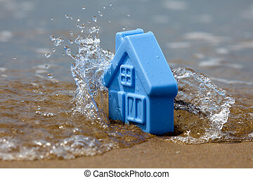 Toy plastic house on the sand washes wave - Blue plastic toy...