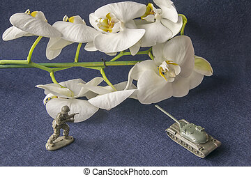 Toy plastic tank and military man with white flower