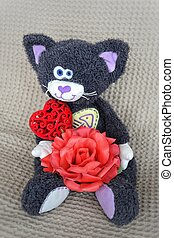toy plush cat sits on a light background and holds a red rose