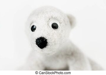 toy polar bear made of felted wool close up on white background