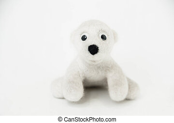 toy polar bear made of felted wool sitting on white background
