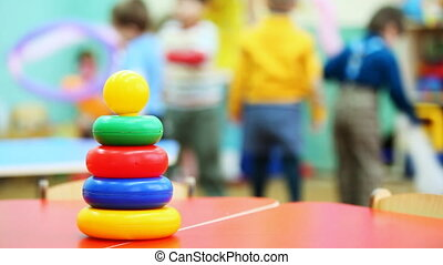 toy pyramid of colored rings stands on table, in defocus behind it children play