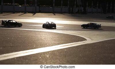 Toy racing machines ride on asphalt