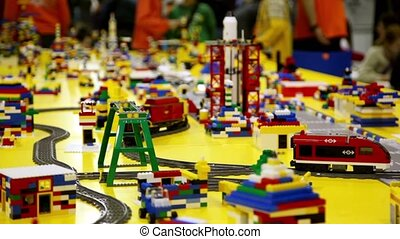Toy railroad among different objects on yellow surface