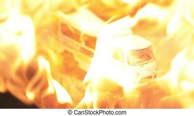 Toy retro Soviet minivan melts under hot fire. Slow motion.