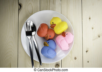 Toy rubber duck on a plate on a wooden floor.