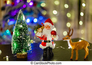 Toy Santa Claus against the background of light garlands
