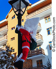 Toy santa claus hanging on a lamp post with a pile of snow on his head