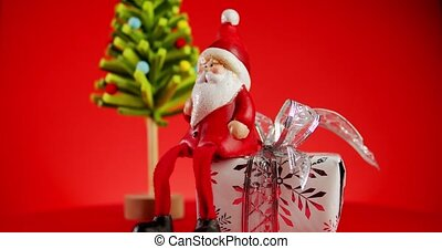 toy santa claus with gift and christmas tree on red background