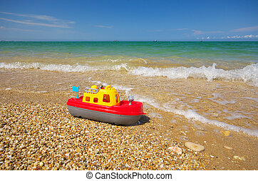Toy ship on the sea shore