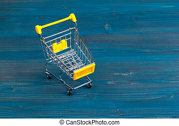 Toy shopping cart on blue wooden background