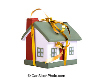 Toy small house with a gold bow. The concept of purchase and sale of habitation.