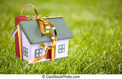 Toy small house with a gold bow. The concept of purchase and...