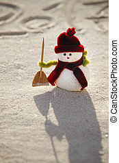 Toy snowman on the sand