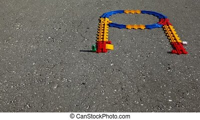 Toy station and railway on asphalt. Time lapse.
