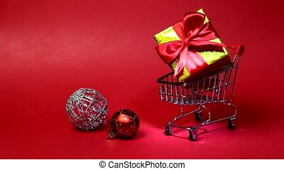 Toy supermarket trolley on red background. The cart has gift box and christmas balls. New Year shopping concept. Red background, place for text.