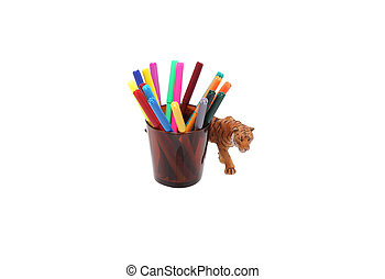 Toy tiger and crayons in a glass.