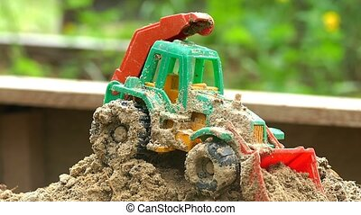 Toy tractor in the sandbox slow motion video - Toy tractor...