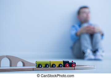 Toy train and little boy - Toy train in a room and sad boy...