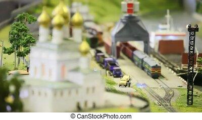 toy train bring empty cargo wagon on rail from storage station in modern toy city near church