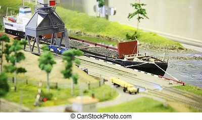 toy train bring empty cargo wagon on rail to storage station in port near transport ship