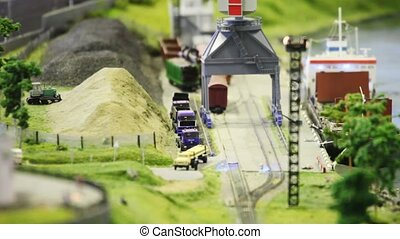 toy train bring empty cargo wagon to loader in storage station near port and transport ship